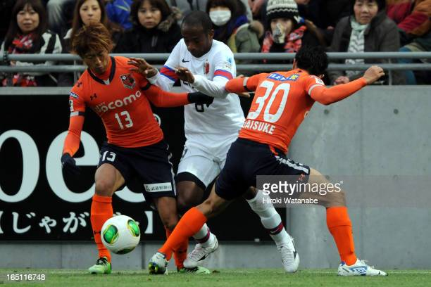 Juninho whose real name is Carlos Alberto Carvalho Dos Anjos Junior of Kashima Antlers competes for the ball against Daigo Watanabe and Daisuke...