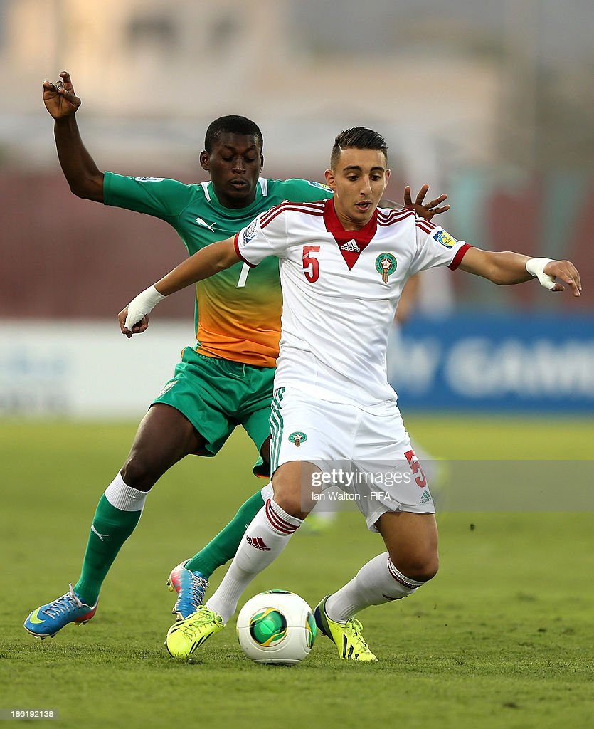 Junior Ahissan of Ivory Coast tries to tackle Achraf Achaoui of Morocco during the Round of 16 match of the FIFA U-17 World Cup between Morocco and Ivory Coast at Fujairah Stadium on October 29, 2013 in Fujairah, United Arab Emirates.