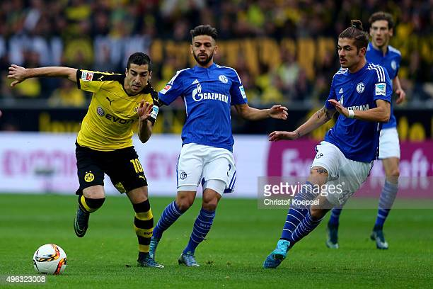 Junior Caicara of Schalke and Roman Neustaedter of Schalke challenge Henrikh Mkhitaryan of Dortmund during the Bundesliga match between Borussia...