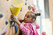 Junior Climber Girl shirt hanging on holds on climbing wall of indoor gym