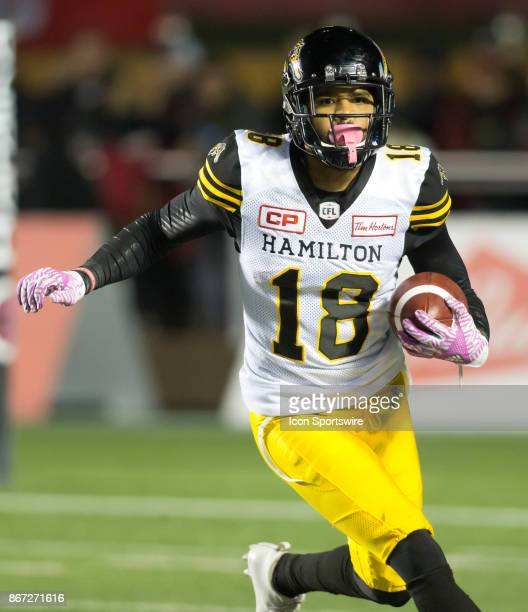 Junior Collins of the Hamilton TigerCats runs the ball upfield against the Ottawa Redblacks in Canadian Football League play at TD Place Stadium in...
