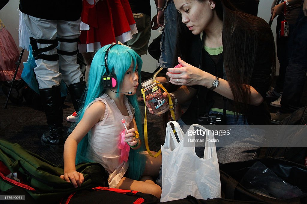 A junior Cosplayer takes a rest after posing for photographers during the final day of AniManGaki on August 25, 2013 in Kuala Lumpur, Malaysia. AniManGaki, which is now into its fifth year, attracts fans of Anime, Manga and Cosplay from across Asia who gather together to celebrate the genre.