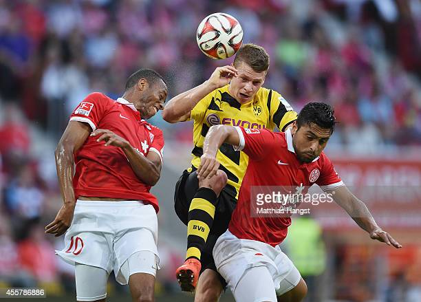 Junior Diaz of Mainz jumps for a header with Lukasz Piszczek of Dortmund and Gonzalo Jara of Mainz during the Bundesliga match between 1 FSV Mainz 05...