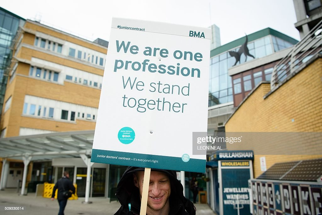 A junior doctor holds a placard on a picket line during a 24-hour strike over pay and conditions outside Whittington hospital in north London on February 10, 2016. Thousands of junior doctors began a second strike at English hospitals on Wednesday against proposed new working conditions and pay rates. Junior doctors -- all medics below consultant level -- were providing emergency care only from 8:00am (0800 GMT) in the 24-hour strike. NEAL