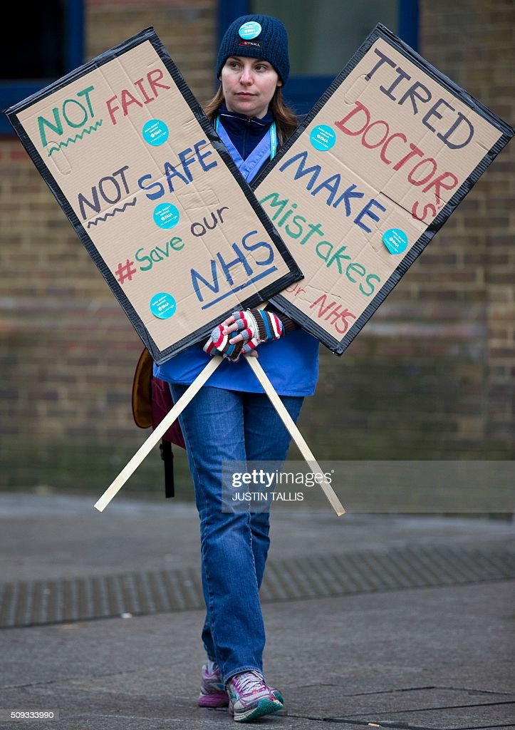 A junior doctor holds placards as they protest outside Guy's Hospital during a 24-hour strike over pay and conditions in London on February 10, 2016. Thousands of junior doctors began a second strike at English hospitals on Wednesday against proposed new working conditions and pay rates. Junior doctors -- all medics below consultant level -- were providing emergency care only from 8:00am (0800 GMT) in the 24-hour strike. / AFP / JUSTIN TALLIS