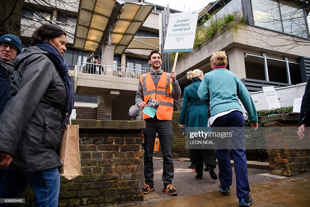 A junior doctor is seen holding a placard on a picket line during a 24-hour strike over pay and conditions outside the Royal Free hospital in north London on February 10, 2016. Thousands of junior doctors began a second strike at English hospitals on Wednesday against proposed new working conditions and pay rates. Junior doctors -- all medics below consultant level -- were providing emergency care only from 8:00am (0800 GMT) in the 24-hour strike. NEAL