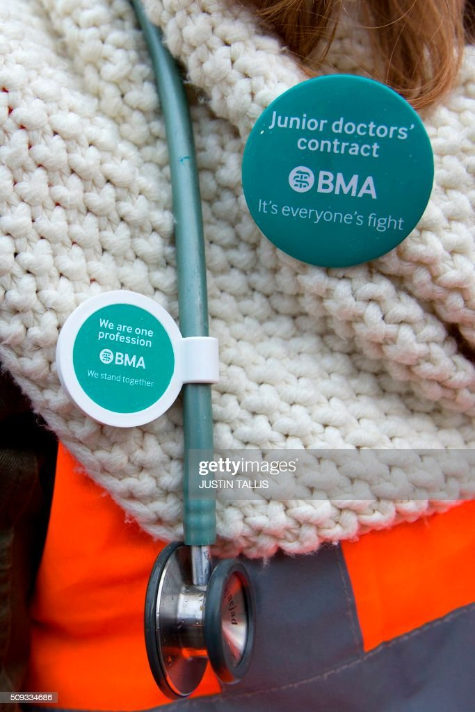 A junior doctor wears a stethoscope and a BMA (British Medical Association) badge outside Maudsley Hospital during a 24-hour strike by junior doctors over pay and conditions in London on February 10, 2016. Thousands of junior doctors began a second strike at English hospitals on Wednesday against proposed new working conditions and pay rates. Junior doctors -- all medics below consultant level -- were providing emergency care only from 8:00am (0800 GMT) in the 24-hour strike. / AFP / JUSTIN TALLIS