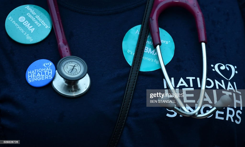 A junior doctor with stethoscope and BMA (British Medical Association) badgesstanding on a picket line during a 24-hour strike over pay and conditions is seen outside St Thomas' Hospital in London on February 10, 2016. Thousands of junior doctors began a second strike at English hospitals on Wednesday against proposed new working conditions and pay rates. Junior doctors -- all medics below consultant level -- were providing emergency care only from 8:00am (0800 GMT) in the 24-hour strike. STANSALL