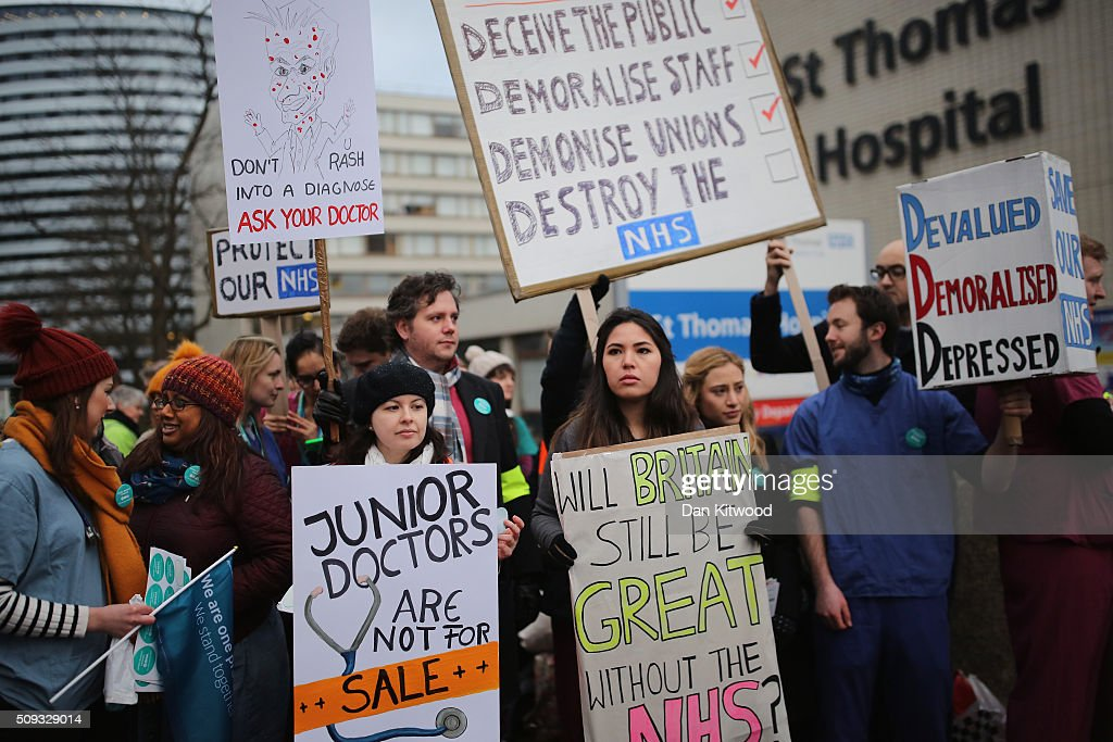 Junior Doctors carry placards on Westminster Bridge as they demonstrate outside St Thomas's Hospital on February 6, 2016, in London, England. Junior Doctors across the United Kingdom began a 24 hour strike today over the British governments' plans to change contracts for junior doctors. Doctors have claimed that Prime Minister David Cameron's government is not providing enough resources for the state-run National Health Service (NHS), which was founded by a socialist government in 1948 to provide free health care at the point of delivery.