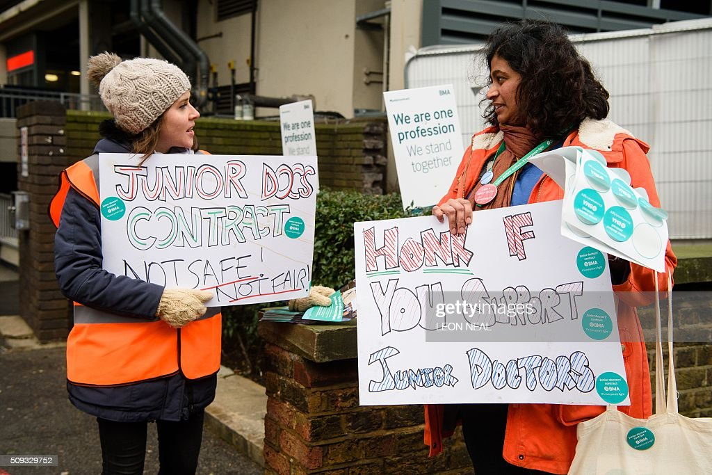 Junior doctors hand out stickers and hold placards on a picket line during a 24-hour strike over pay and conditions outside the Royal Free hospital in north London on February 10, 2016. Thousands of junior doctors began a second strike at English hospitals on Wednesday against proposed new working conditions and pay rates. Junior doctors -- all medics below consultant level -- were providing emergency care only from 8:00am (0800 GMT) in the 24-hour strike. NEAL