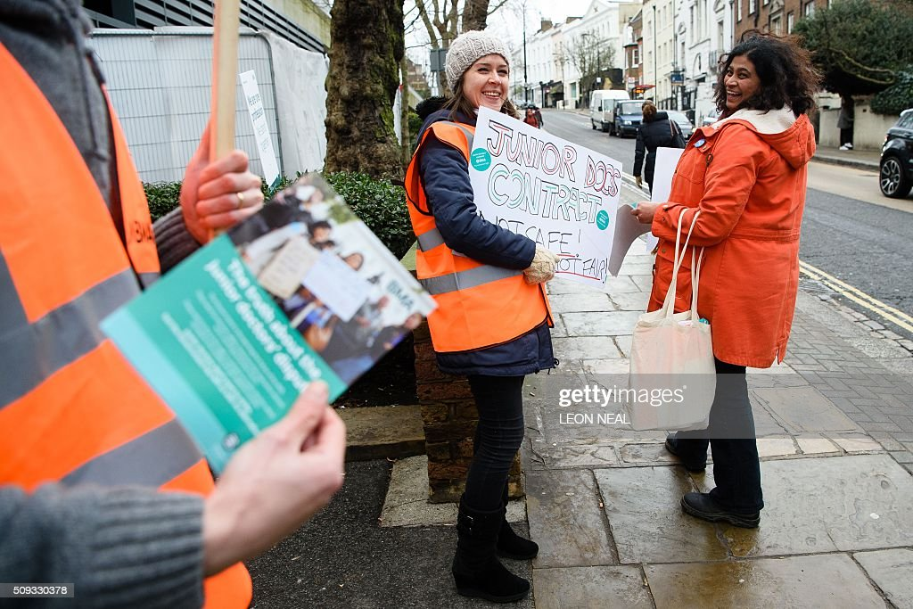 Junior doctors hand out stickers and leaflets while holding placards on a picket line during a 24-hour strike over pay and conditions outside the Royal Free hospital in north London on February 10, 2016. Thousands of junior doctors began a second strike at English hospitals on Wednesday against proposed new working conditions and pay rates. Junior doctors -- all medics below consultant level -- were providing emergency care only from 8:00am (0800 GMT) in the 24-hour strike. NEAL