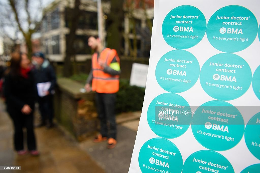 Junior doctors hand out stickers on a picket line during a 24-hour strike over pay and conditions outside the Royal Free hospital in north London on February 10, 2016. Thousands of junior doctors began a second strike at English hospitals on Wednesday against proposed new working conditions and pay rates. Junior doctors -- all medics below consultant level -- were providing emergency care only from 8:00am (0800 GMT) in the 24-hour strike. NEAL