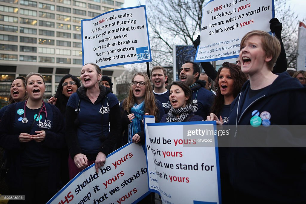A Junior Doctors NHS choir sing and protest outside St Thomas's Hospital on February 6, 2016, in London, England. Junior Doctors across the United Kingdom began a 24 hour strike today over the British governments' plans to change contracts for junior doctors. Doctors have claimed that Prime Minister David Cameron's government is not providing enough resources for the state-run National Health Service (NHS), which was founded by a socialist government in 1948 to provide free health care at the point of delivery.