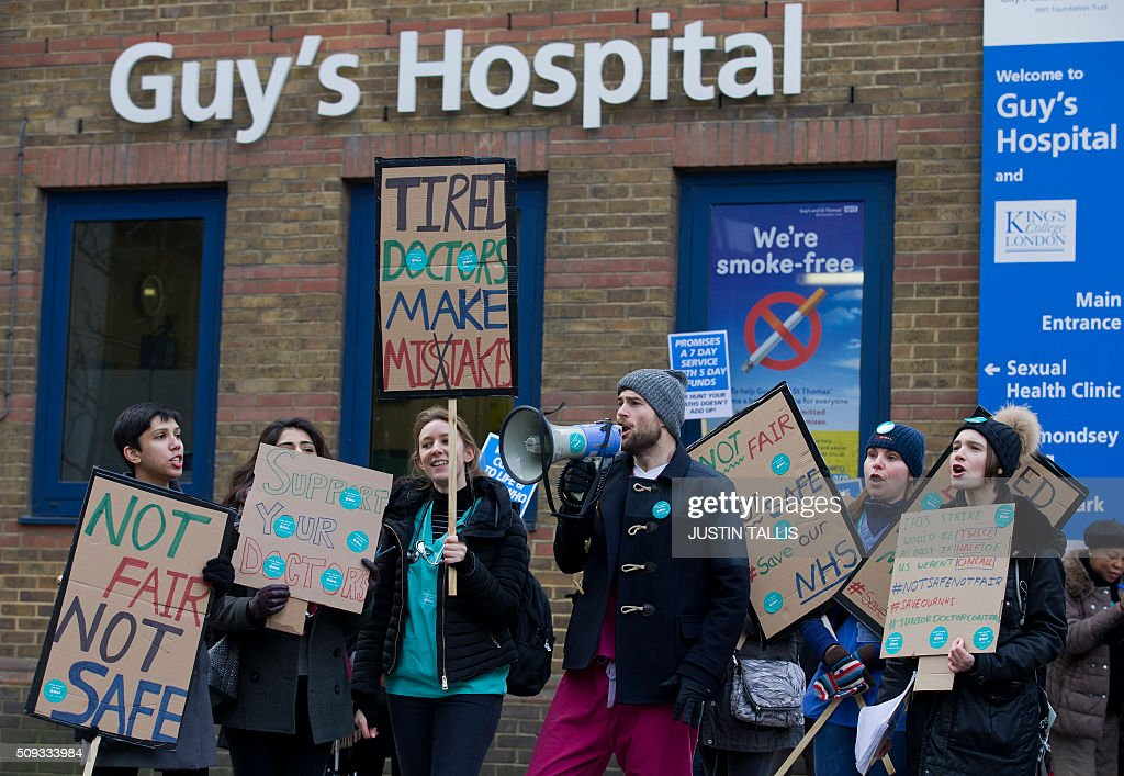 Junior doctors shout slogans and hold placards as they protest outside Guy's Hospital during a 24-hour strike over pay and conditions in London on February 10, 2016. Thousands of junior doctors began a second strike at English hospitals on Wednesday against proposed new working conditions and pay rates. Junior doctors -- all medics below consultant level -- were providing emergency care only from 8:00am (0800 GMT) in the 24-hour strike. / AFP / JUSTIN TALLIS