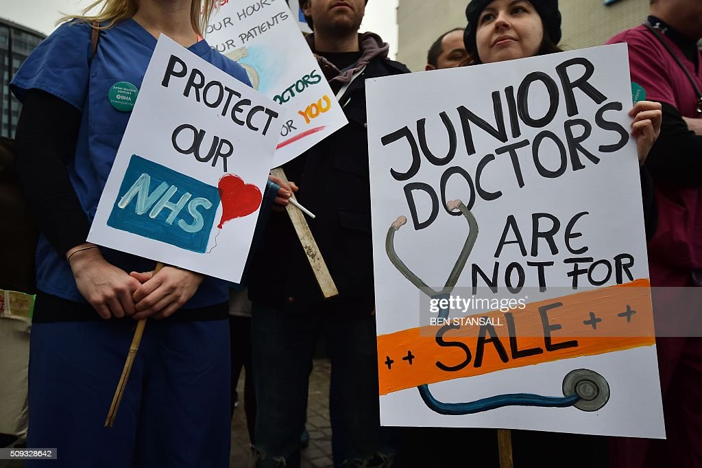 Junior doctors stand with placards as they stand on a picket line during a 24-hour strike over pay and conditions outside St Thomas' Hospital in London on February 10, 2016. Thousands of junior doctors began a second strike at English hospitals on Wednesday against proposed new working conditions and pay rates. Junior doctors -- all medics below consultant level -- were providing emergency care only from 8:00am (0800 GMT) in the 24-hour strike. STANSALL