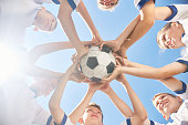 Low angle view of boys in junior football team standing in circle holding ball together against clear blue sky