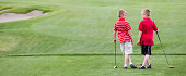 A couple of young boys bonding on the golf course. Friendship theme.