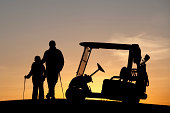 A junior golfer with his dad. Horizontal colour image. Silhouette. Golf concept.