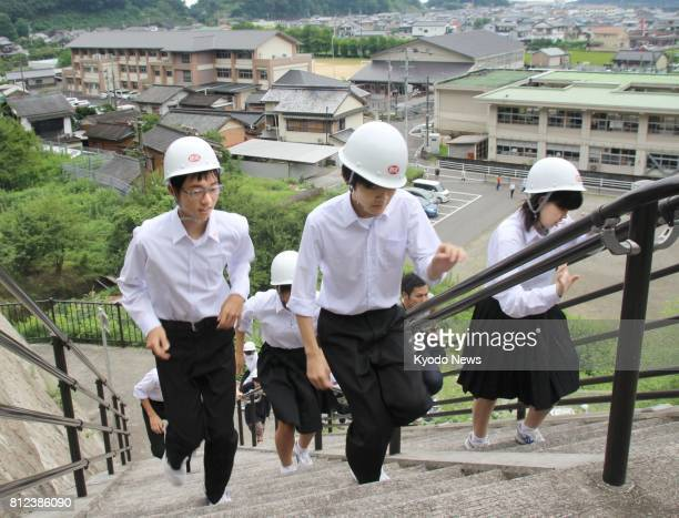Junior high school students in the southwestern Japan town of Kuroshio head for higher ground on July 11 during an emergency drill to prepare for...