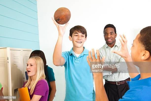 Junior high students around lockers backpacks football