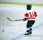 Side view of junior ice hockey player during practice or game. The boy is wearing red and white jersey, black trunks and helmet.