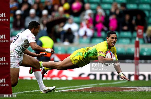 Junior Laloifi of Australia dives over the line to score a try ahead of Marcus Watson of England during the Marriott London Sevens Day Two at...