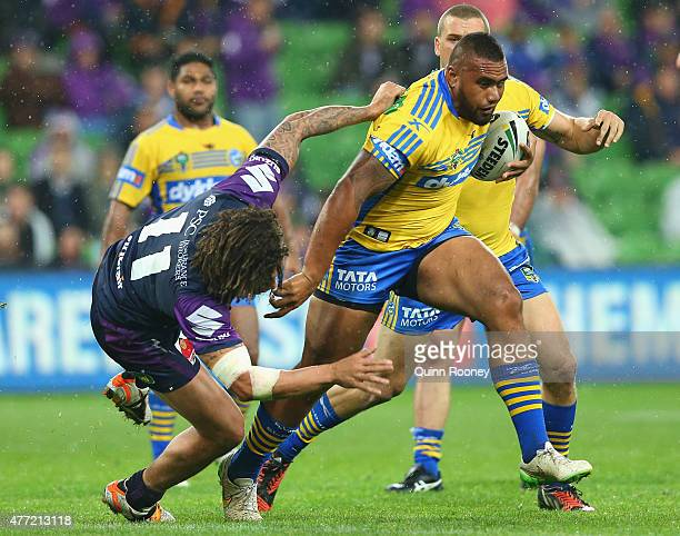 Junior Paulo of the Eels fends off a tackle by Kevin Proctor of the Storm during the round 14 NRL match between the Melbourne Storm and the...