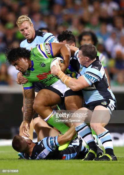 Junior Paulo of the Raiders is tackled during the round two NRL match between the Canberra Raiders and the Cronulla Sharks at GIO Stadium on March 11...