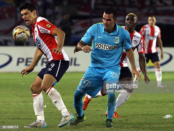 Junior player Roberto Ovelar vies for the ball with Nacional player Alejandro Bernal during their Colombian Football League first leg final match on...