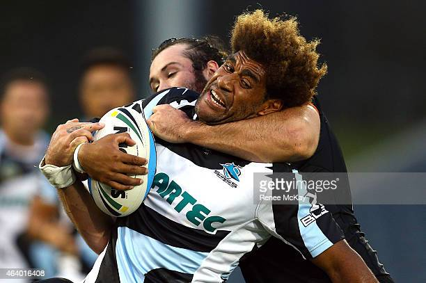 Junior Roqica of the Sharks is tackled by Aaron Woods during the NRL Trial Match between the Wests Tigers and the Cronulla Sharks at Campbelltown...