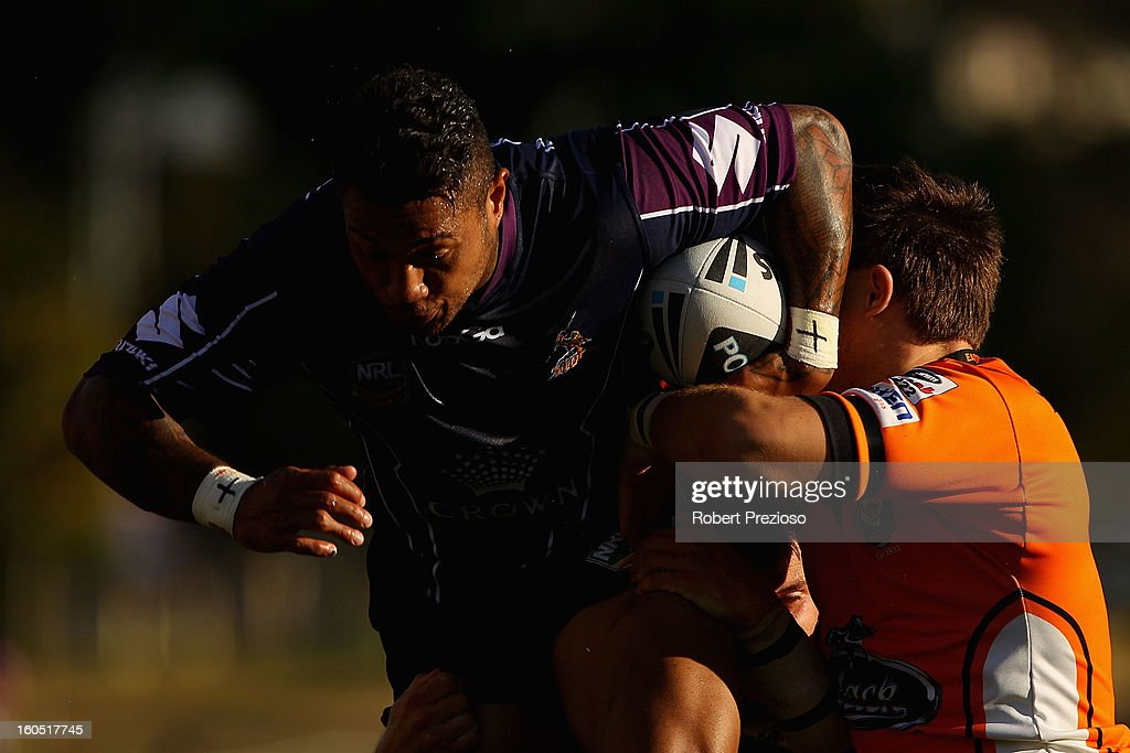Junior Sa'u of the Storm is tackled during the NRL trial match between the Melbourne Storm and Brisbane Easts at Gosch's Paddock on February 2, 2013 in Melbourne, Australia.