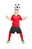 Full length portrait of a junior soccer player joggling with a ball isolated on white background