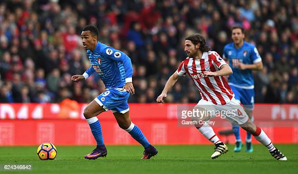 Junior Stanislas of AFC Bournemouth is chased down by Joe Allen of Stoke City during the Premier League match between Stoke City and AFC Bournemouth...