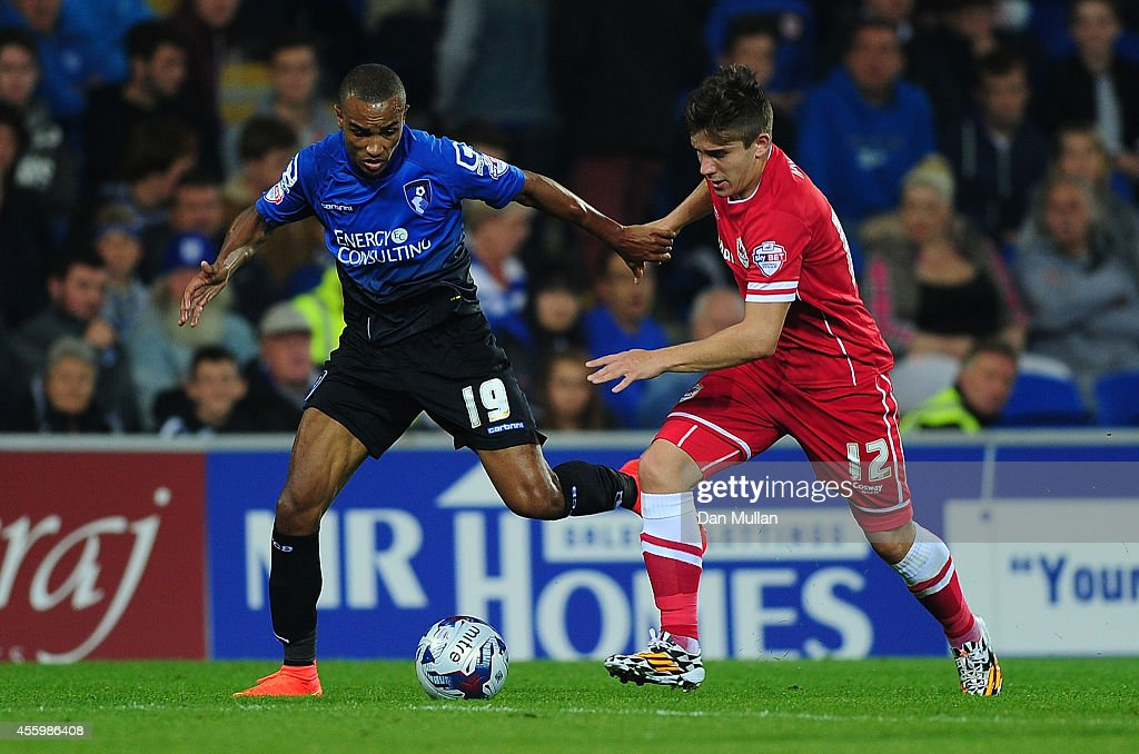 Junior Stanislas of Bournemouth (L) battles for the ball with Declan John of Cardiff City during the Capital One Cup third round match between Cardiff City and Bournemouth at Cardiff City Stadium on September 23, 2014 in Cardiff, Wales.