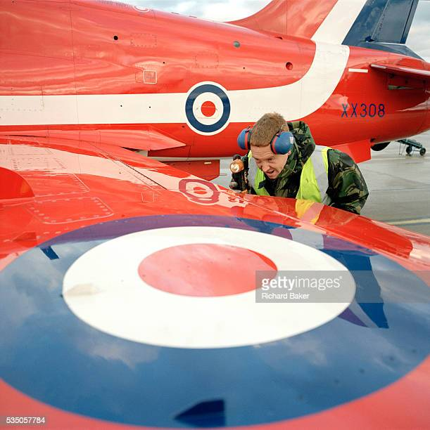 Junior Technician Brian Robb an engineer with the elite 'Red Arrows' Britain's prestigious Royal Air Force aerobatic team shines his torch inside the...