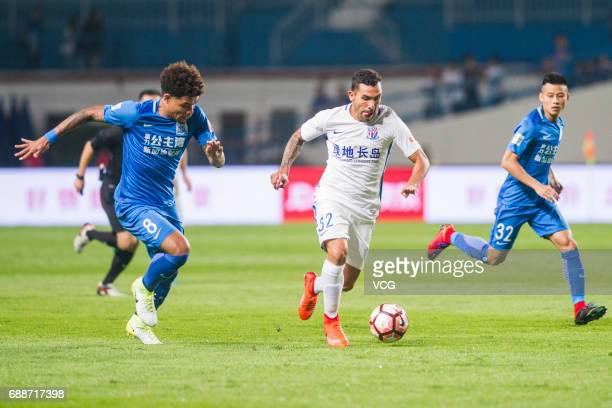 Junior Urso of Guangzhou RF and Carlos Tevez of Shanghai Shenhua compete for the ball during the 11th round match of China Super League between...
