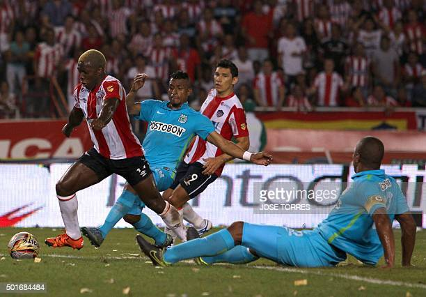 Junior's player Edinson Toloza vies for the ball with Nacional's player Farid Diaz during a Colombian Football League first leg final match on...