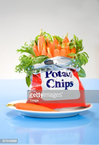Junk food bag of baby carrots on plate : Stock Photo