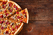 Junk food, bad habits, Pizza sliced on rustic wooden table background, flat lay. Italian cuisine concept