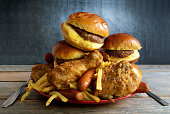 Huge portion of junk food on a plate including burgers, fries, chicken and hot dogs