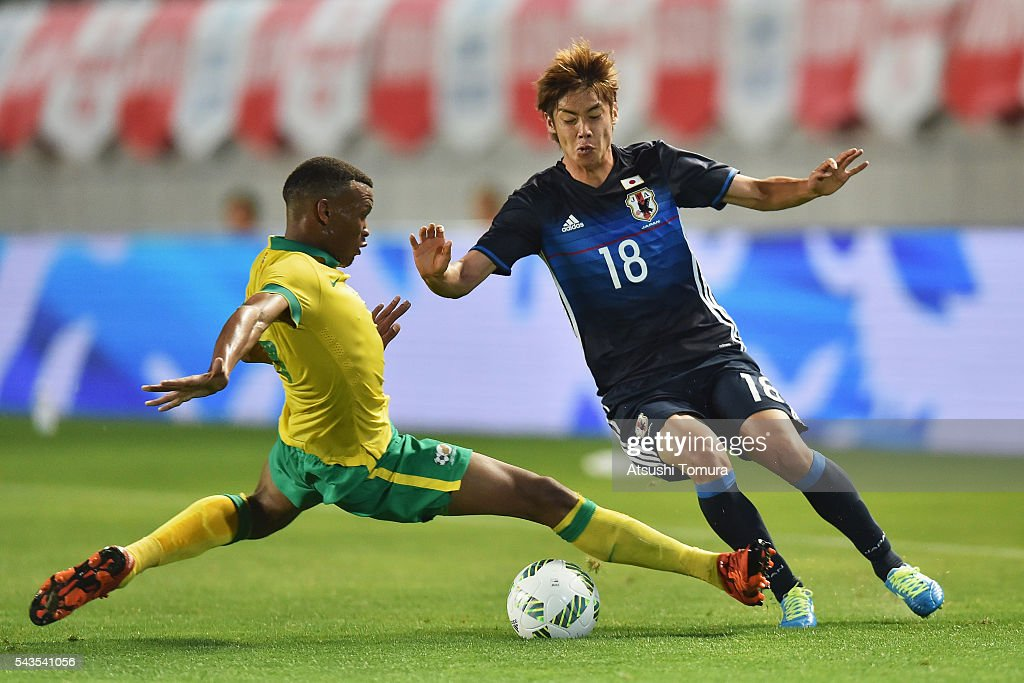 Junya Ito of Japan is challenged by Mothiba Mvalo of South Africa during the U-23 international friendly match between Japan and South Africa at the Matsumotodaira Football Stadium on June 29, 2016 in Matsumoto, Nagano, Japan.