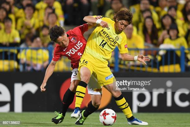 Junya Ito of Kashiwa Reysol and Tomoya Ugajin of Urawa Red Diamonds compete for the ball during the JLeague J1 match between Kashiwa Reysol and Urawa...