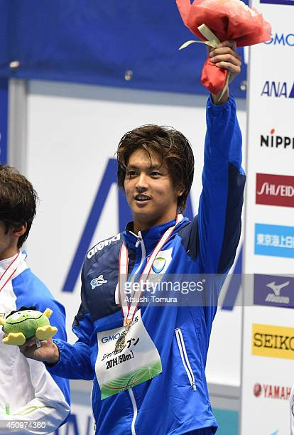 Junya Koga of Japan celebrates on the podium after winning the men 50m Backstroke during day three of the Japan Open 2014 at Tokyo Tatsumi...