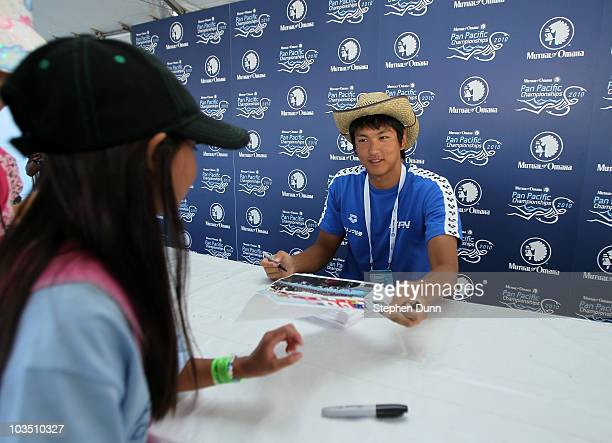 Junya Koga of Japan signs an autograph during the Mutual of Omaha Pan Pacific Championships at the William Woollett Jr Aquatic Center on August 20...