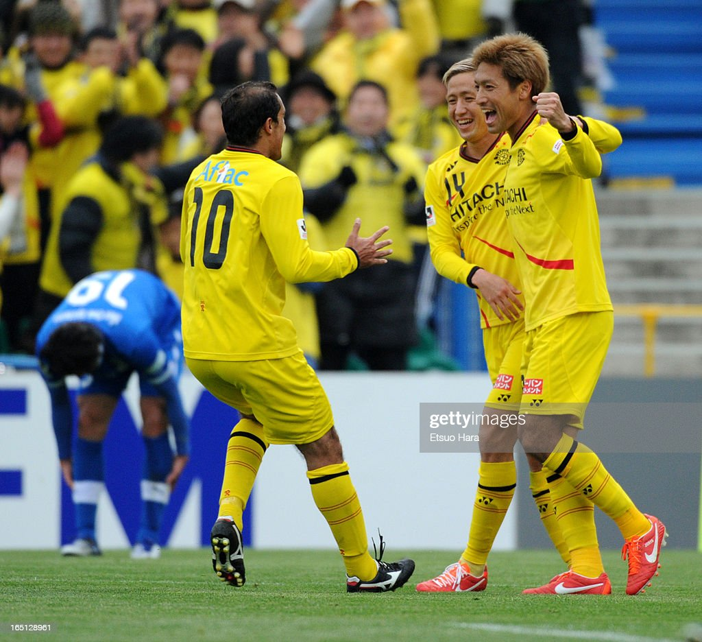 Junya Tanaka (1R) of Kashiwa Reysol celebrates scoring the second goal with his team mates Kenta Kano (C) and <a gi-track='captionPersonalityLinkClicked' href=/galleries/search?phrase=Leandro+Domingues&family=editorial&specificpeople=5957600 ng-click='$event.stopPropagation()'>Leandro Domingues</a> during the J.League match between Kashiwa Reysol and Oita Trinita at Hitachi Kashiwa Soccer Stadium on March 30, 2013 in Kashiwa, Chiba, Japan.