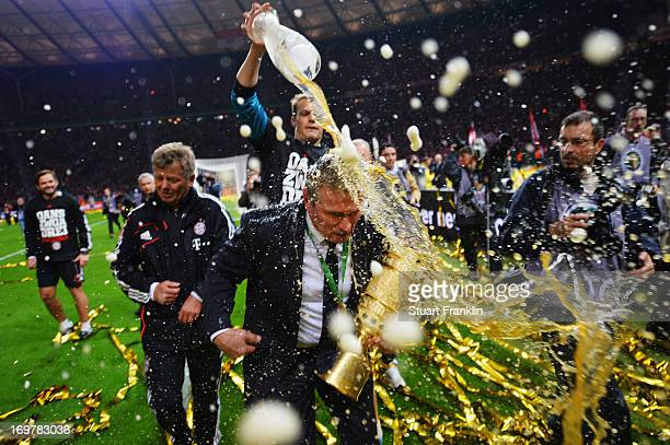 Jupp Heynckes head coach of Bayern Muenchen is showered with beer by Manuel Neuer as he celebrates victory in his last match after the DFB Cup Final...
