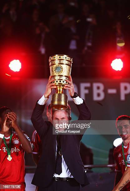 Jupp Heynckes head coach of Bayern Muenchen lifts the trophy to celebrate victory in his last match after the DFB Cup Final match between FC Bayern...
