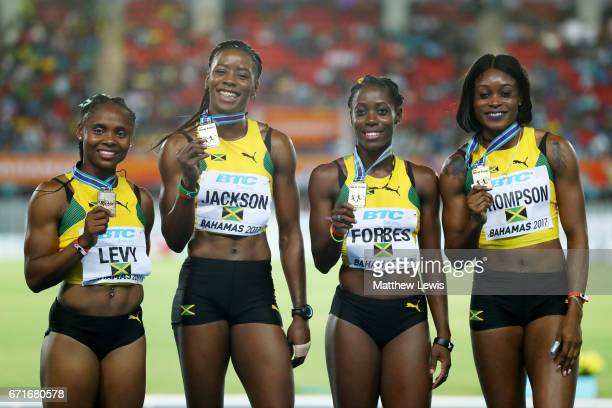 Jura Levy Shericka Jackson Sashalee Forbes and Elaine Thompson of Jamaica pose on the podium after finishing first in the Women's 4 x 200 Meters...