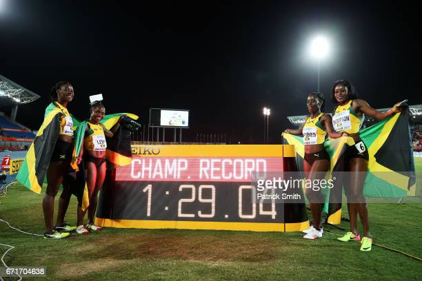 Jura Levy Shericka Jackson Sashalee Forbes and Elaine Thompson of Jamaica pose after setting a new championship record of 12904 in the Women's 4 x...