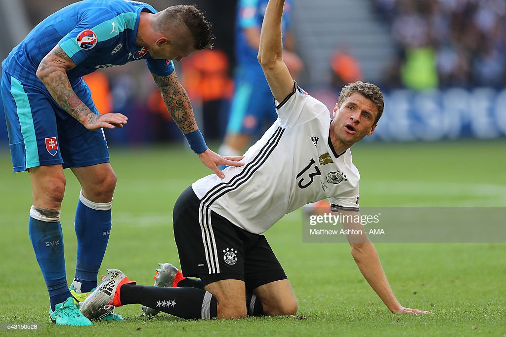 <a gi-track='captionPersonalityLinkClicked' href=/galleries/search?phrase=Juraj+Kucka&family=editorial&specificpeople=6388600 ng-click='$event.stopPropagation()'>Juraj Kucka</a> of Slovakia gets his laces tangled with Thomas Muller of Germany during the UEFA Euro 2016 Round of 16 match between Germany and Slovakia at Stade Pierre-Mauroy on June 26, 2016 in Lille, France.